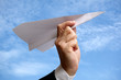Business man with paper airplane against blue sky