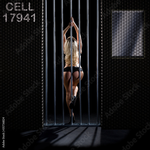 beautiful woman locked in a prison cell