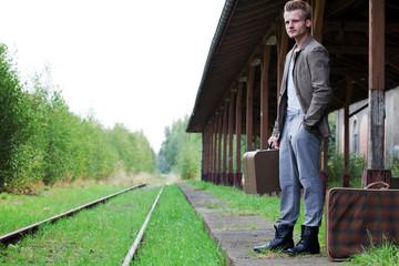 Mann steht mit Koffer am Bahngleis