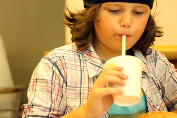 Boy eating hamburger in fast food restaurant, steadicam shot