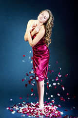 Beautiful young woman with rose flower petals