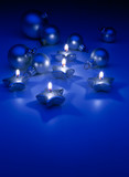 Fototapety Art Christmas candles and ornaments on a blue background