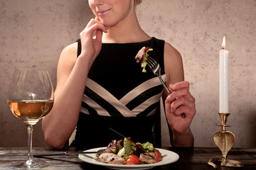 A young woman eating meat salad with vegetables at a table in a