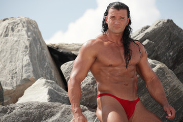 Muscular bodybuilder posing on the rocks