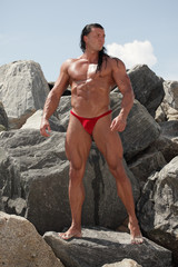 Image of a muscular man posing on the rocks