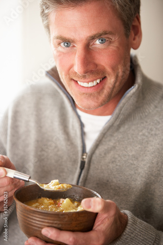 Man eating bowl of soup