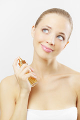 Young woman spraying perfume. on gray background