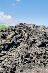 sharp hardened lava rocks with Etna on background