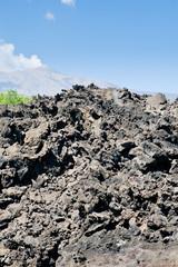 sharp hardened lava rocks with Etna on background