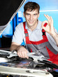 Master mechanic is satisfied with his job in a garage
