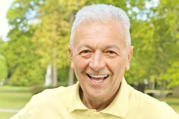 Portrait of smiling senior man in the park
