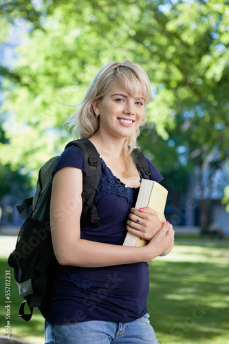 smiling college girl with book and bag