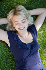 Smiling young woman lying on grass