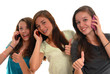 Three teenage girls smiling together with cell phones