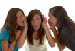 Teenage girls sharing secrets one is shocked others whispering.