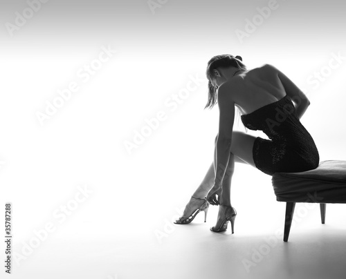 Sexy woman sits on chair, and prepares