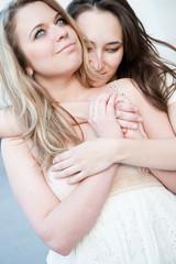 Two young beautiful hugging girls