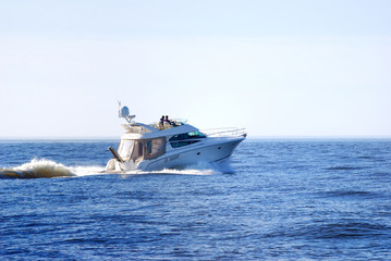 white luxury yacht sailing at great speed