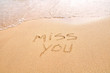 Miss you text written on the beach sand