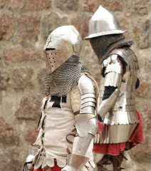 Knights in an armor and with the weapon against a stone wall