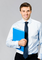 Portrait of business man with folder, over gray