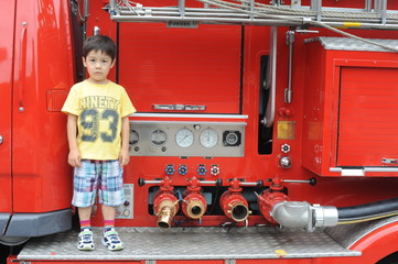 Young boy standing on a fire engine