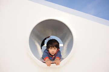 Young boy inside a hole stretching his arms to get out