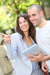 Young couple in public park with electronic tablet