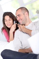 Young couple at home listening to music on internet