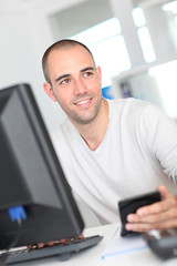 Smiling office worker sitting in front of desktop computer