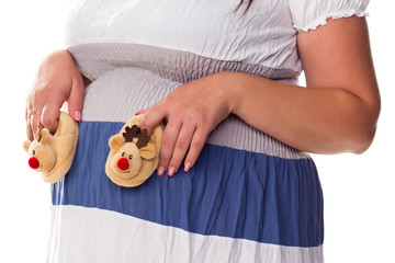Pregnant woman holing baby's bootees at her belly