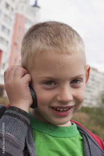 The little boy talks by a mobile phone