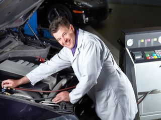 Motor mechanic tuning the engine of a car in a garage