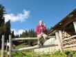 Frau mit lila Jacke sitzt auf Zaun