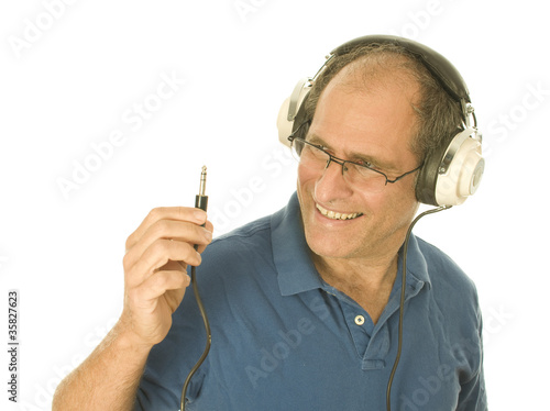 senior man wearing music head phones looking at plug