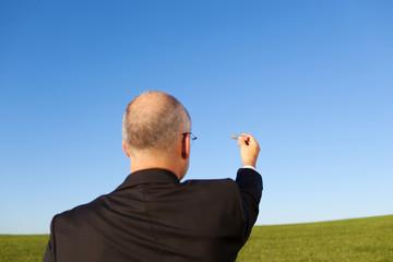 mann zeichnet etwas in den blauen himmel