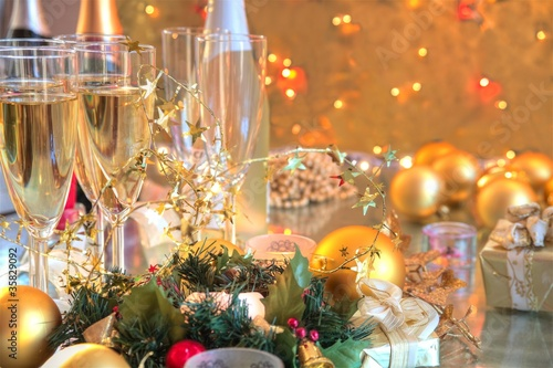 Champagne in glasses,baubles,candle lights.