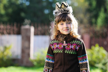 Outdoors portrait of adorable girl wearing crown