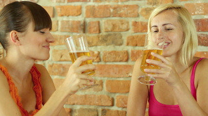 Two female friends talking and drinking beer