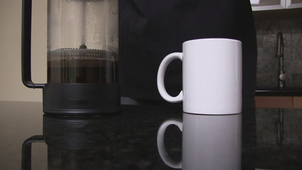 Coffee prepared in a french press poured into a white mug.