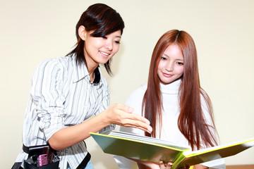 ヘアカタログを見て髪型を確認する女性