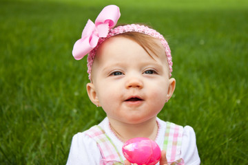 Adorable baby holding a pink Easter egg