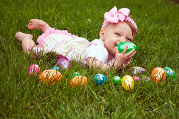 Baby girl laying in the grass with colored Easter eggs