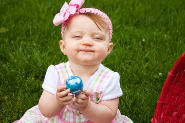 Small child holding a blue Easter egg while smirking