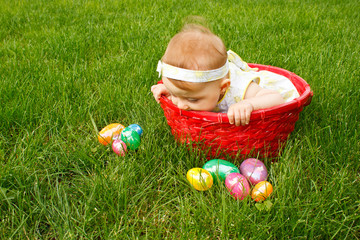 Baby in red basket peeking over the side at Easter eggs