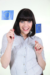 portrait of jovial brunette holding European flags