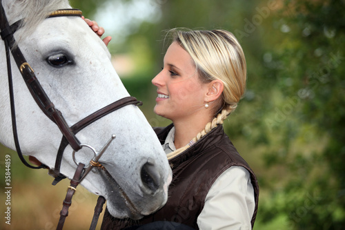 Young woman patting her horse