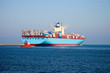 Container ship leaves the port, assist by a tugboat.