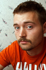 Young man with mustache in orange shirt