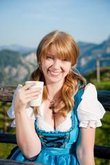 Frau im Dirndl trinkt Milch